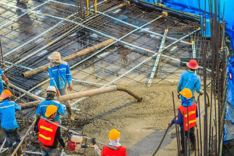 I muratori stanno versando il calcestruzzo in floori di post-tensione fotografie stock