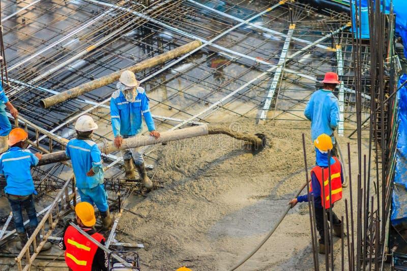 I muratori stanno versando il calcestruzzo in floori di post-tensione fotografia stock libera da diritti