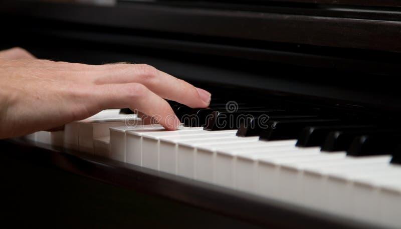 I muziekmaker! De foto van de close-up van pianospeler stock foto
