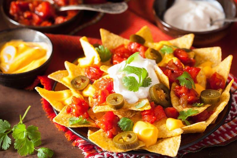 I nacho hanno caricato con salsa, formaggio ed il jalapeno fotografia stock libera da diritti