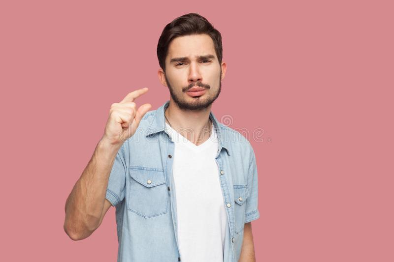 I need a few more. Portrait of hopeful handsome bearded young man in blue casual style shirt standing and looking at camera and. Begging for something. indoor stock image