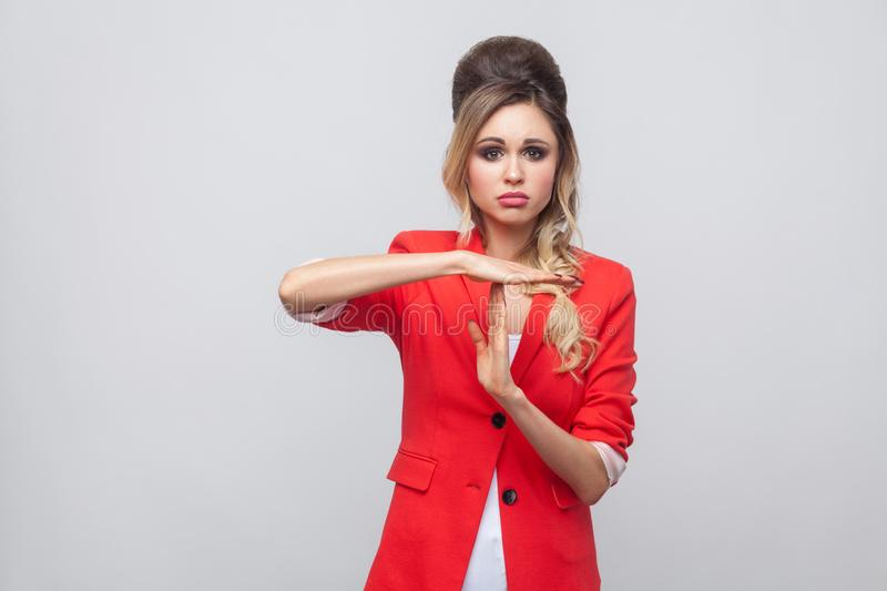 I need more time. Worry beautiful business lady with hairstyle and makeup in red fancy blazer, standing and looking at camera with. Timeout gesture. indoor stock photography