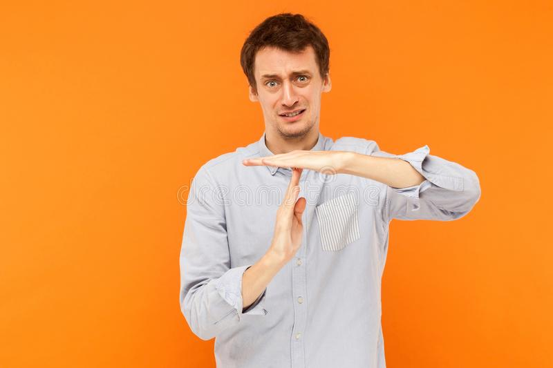 I need time out. Unhappy man showing stop sign at camera. Studio shot, orange background stock photo