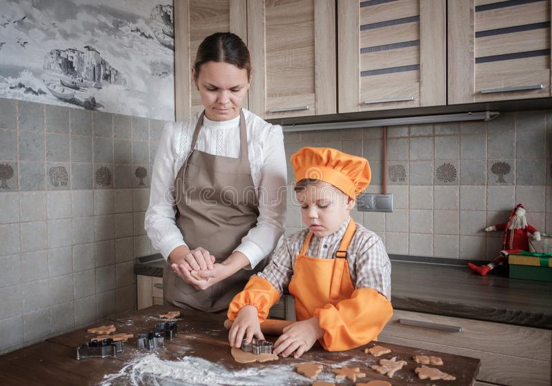Mom and son cook ginger cookies in the kitchen for the new year and Christmas. stock photography