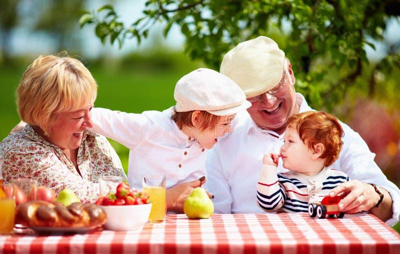 I nonni felici con i nipoti che si siedono allo scrittorio in primavera fanno il giardinaggio fotografie stock