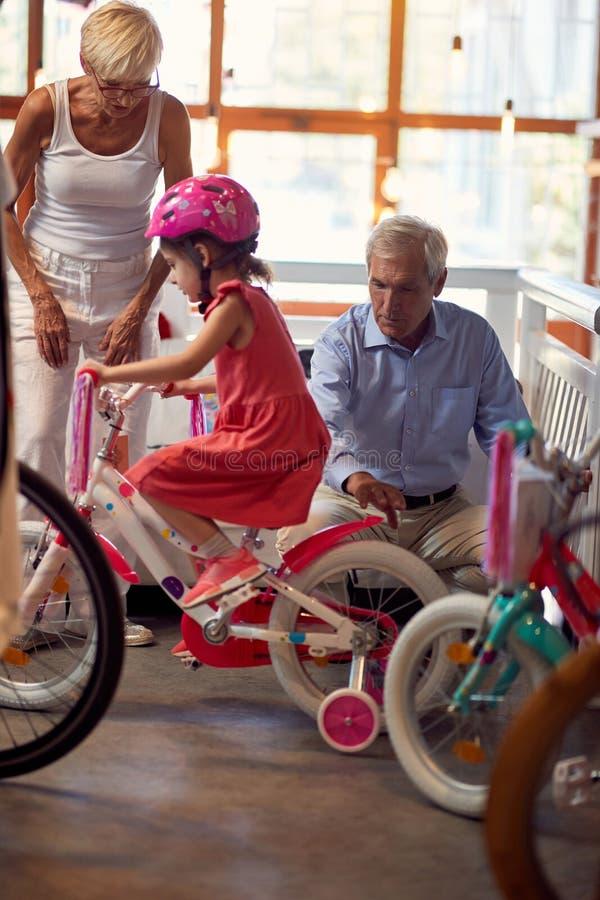 I nonni sceglie la bicicletta nel negozio della bici la loro nipote del bambino immagine stock libera da diritti