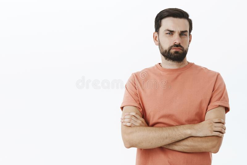 I not believe you. Portrait of suspicious defensive and doubtful 30s male with beard squinting hesitant and intense. Cross hands over chest, frowning and royalty free stock photos