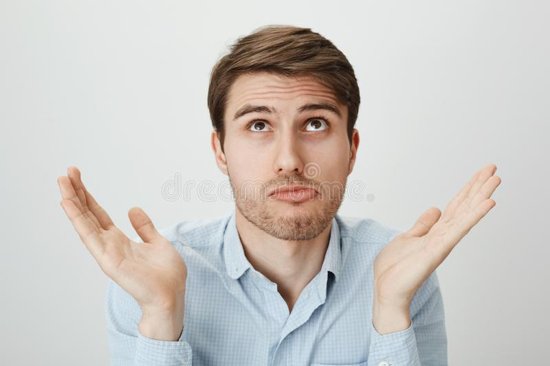I am not involved, this hands are pure. Indoor portrait of handsome confused guy shrugging with raised palms, looking up. And puckering as if making mistake and royalty free stock photo