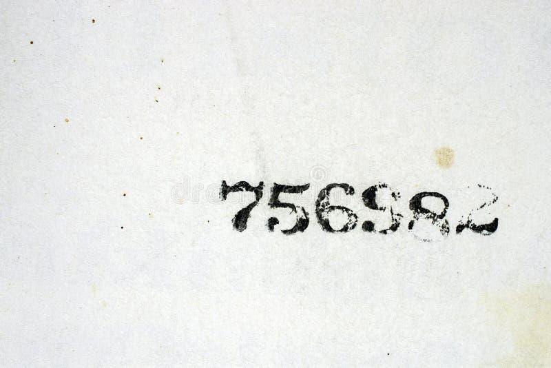 I numeri neri hanno timbrato ad una pagina d'annata macchiata del libro fotografia stock