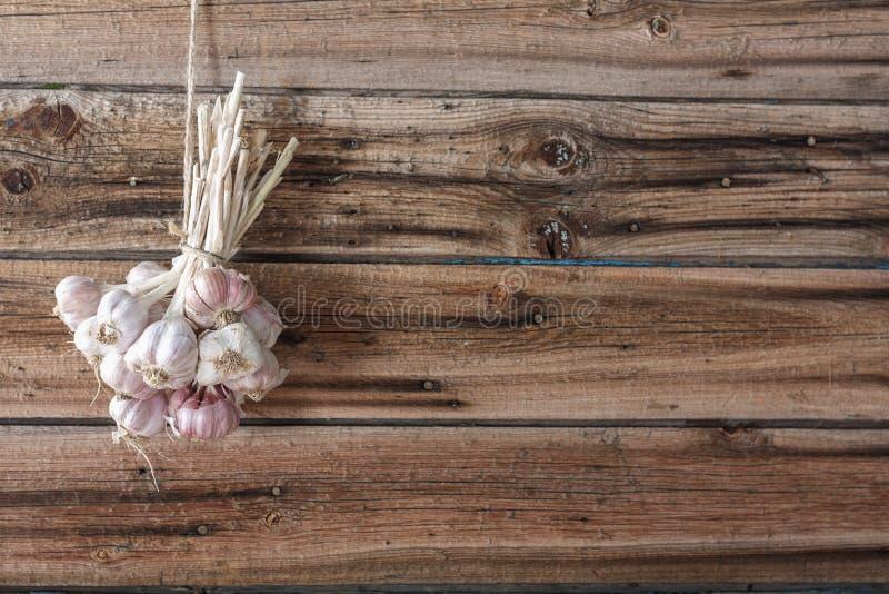 I pacchi di aglio fresco si sono asciugati sulla parete di legno d'annata fotografia stock