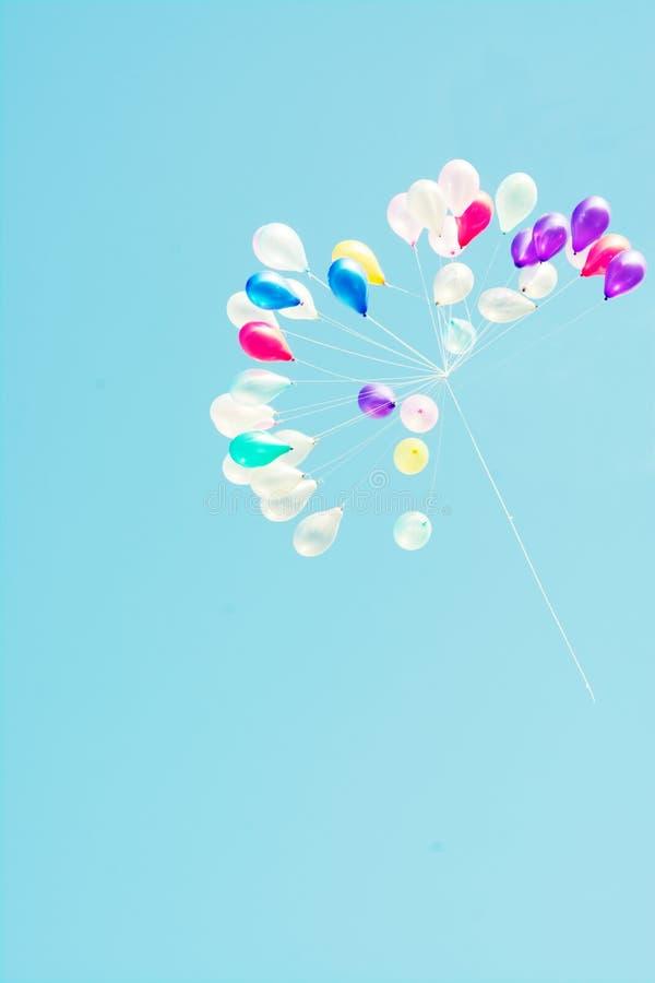 I palloni variopinti con il fondo e l'annata del cielo blu filtrano fotografia stock libera da diritti