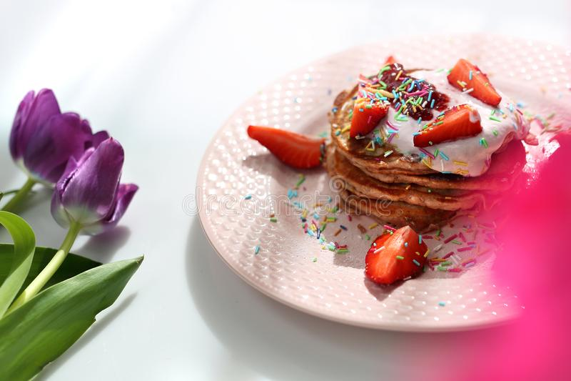 I pancake dolci con le fragole, la ricotta e lo zucchero variopinto spruzza immagini stock