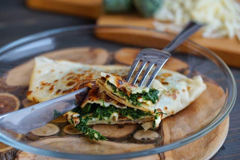 I pancake hanno riempito di spinaci e di formaggio sulla superficie di legno fotografie stock