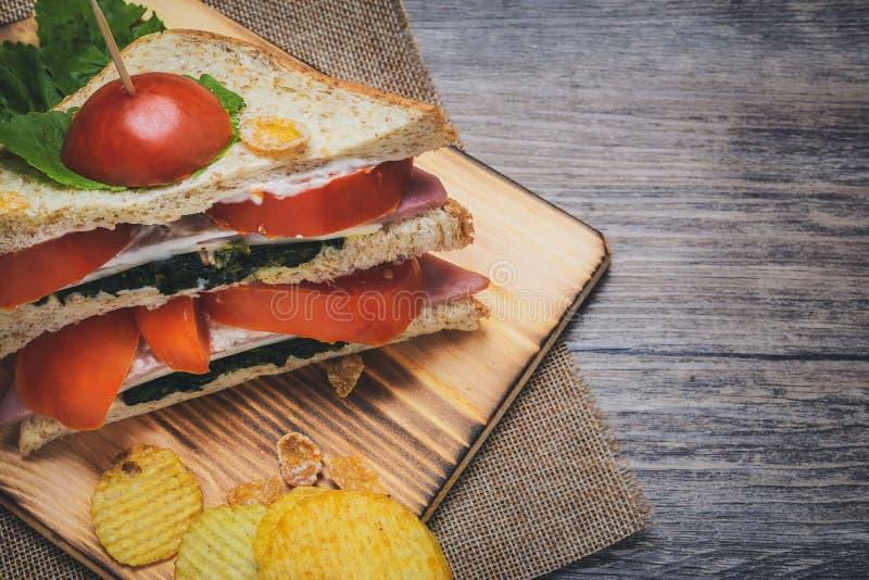 I panini con spinaci ed i pomodori hanno salsa crema sul pavimento di legno che sembra invitante immagini stock