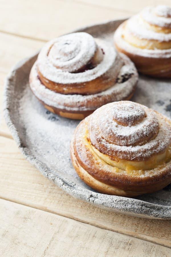 I panini saporiti sono spruzzati con la polvere dello zucchero su una luce fatta a mano immagini stock libere da diritti