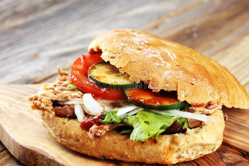 I panini tirati della carne di maiale con il BBQ sauce, cavolo e sottaceti sul wo immagine stock