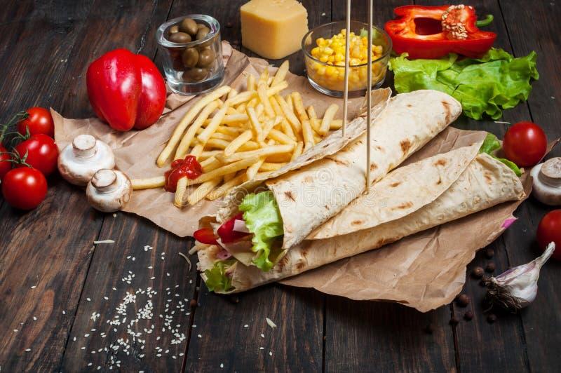 I panini torti rotolano la tortiglia due pezzi e patate fritte su un fondo di legno immagini stock