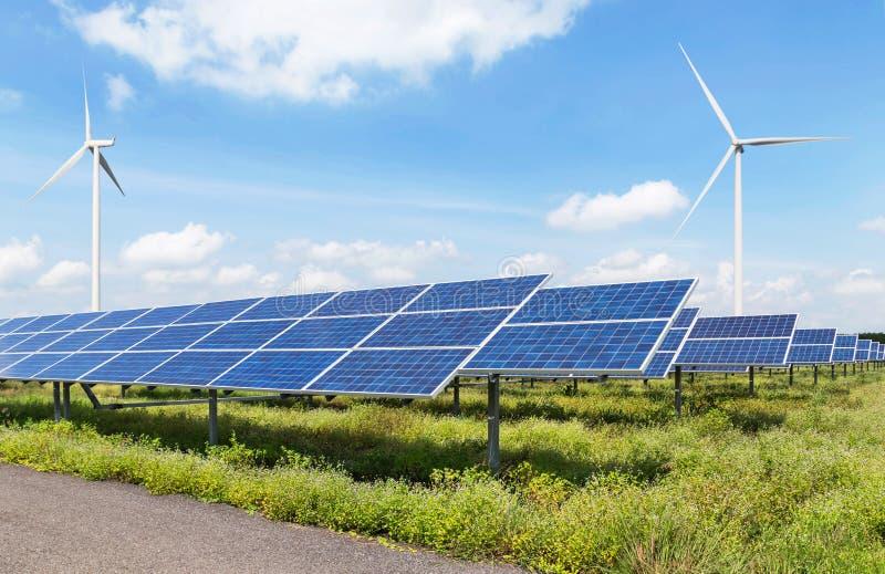 I pannelli solari ed i generatori eolici nella centrale elettrica si inverdiscono l'energia rinnovabile con il fondo del cielo bl fotografia stock