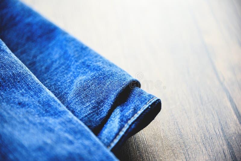 i pantaloni hanno piegato il tessuto del modello dei jeans usato delle blue jeans su fondo di legno fotografie stock