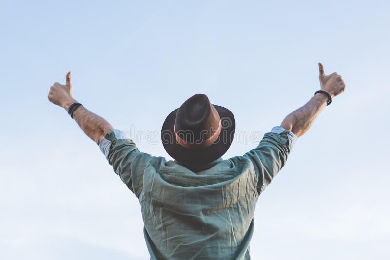 I pantaloni a vita bassa barbuti felici bei che esaminano il cielo blu e gesture le sue mani nel simbolo giusto Concetto di sorve immagini stock