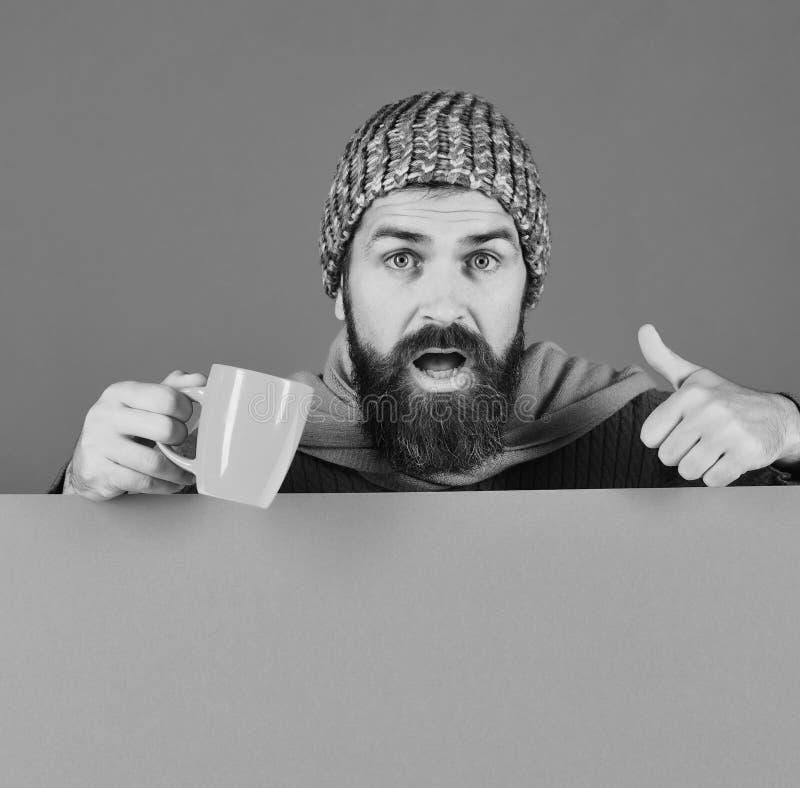 I pantaloni a vita bassa con la barba ed il fronte occupato mostrano i pollici su fotografia stock
