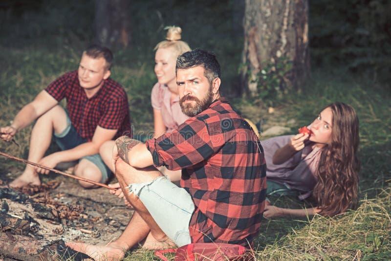 I pantaloni a vita bassa con la barba si rilassano con gli amici nell'uomo barbuto della foresta in camicia di plaid sulla natura fotografia stock