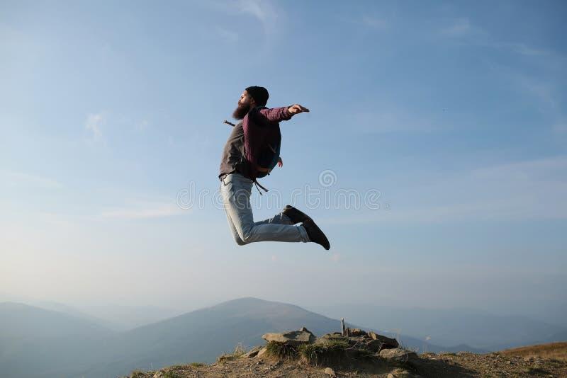 I pantaloni a vita bassa dell'uomo saltano con lo zaino fotografia stock libera da diritti