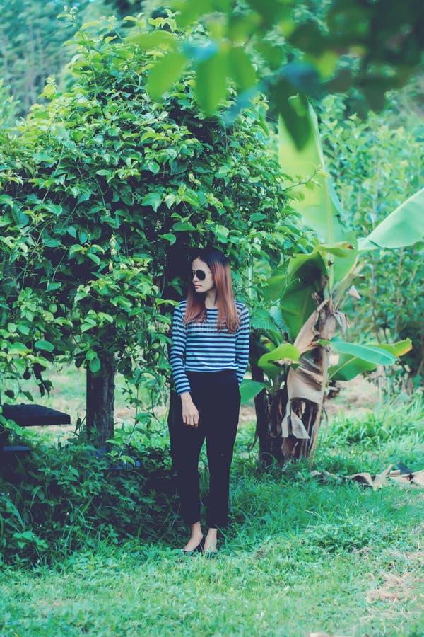 I pantaloni a vita bassa della donna con gli occhiali da sole adattano il concetto di stile di vita di stile, portante una maglie fotografia stock