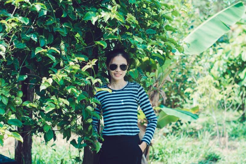 I pantaloni a vita bassa della donna con gli occhiali da sole adattano il concetto di stile di vita di stile, portante una maglie fotografia stock libera da diritti