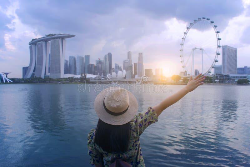 I pantaloni a vita bassa della donna devono godere buona della vista viaggiare e fare un giro turistico a Singapore immagine stock