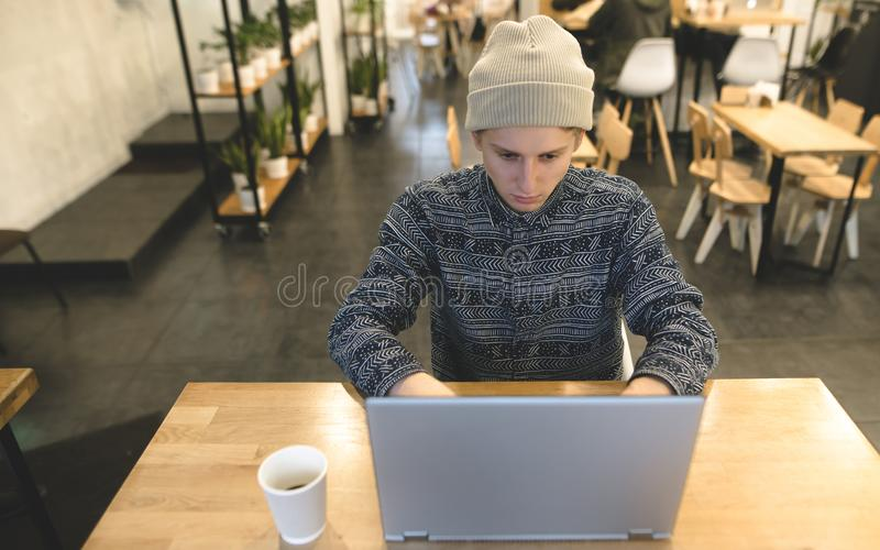 I pantaloni a vita bassa freelance impianti in un caffè accogliente per un computer portatile Uno studente utilizza un computer p fotografia stock libera da diritti