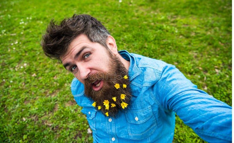 I pantaloni a vita bassa sul fronte allegro si siedono su erba, defocused L'uomo con la barba gode della molla, fondo verde del p fotografia stock