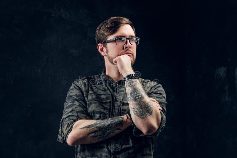 I pantaloni a vita bassa tatuati pensierosi sembrano sinistri e tengono una mano vicino al mento fotografia stock
