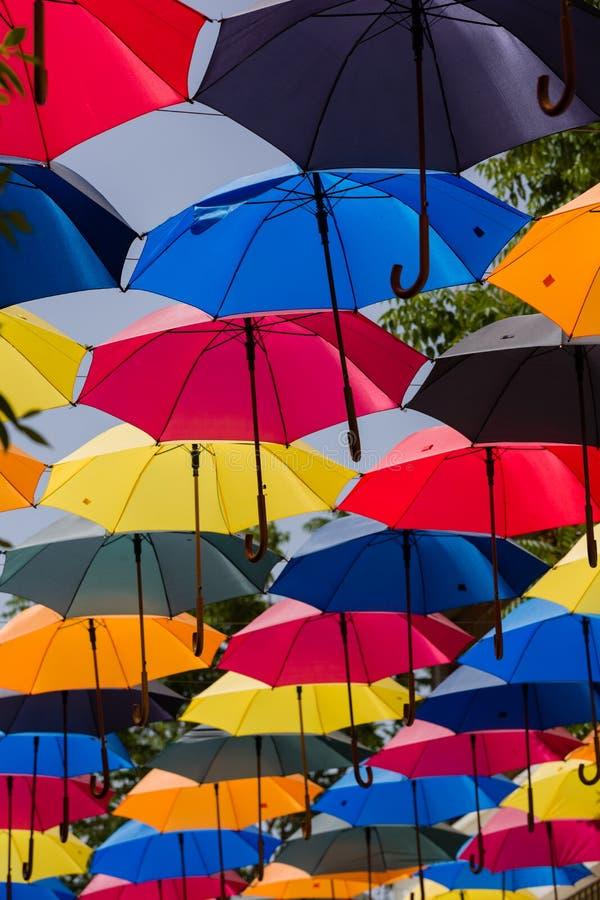 I parasoli variopinti insieme, sopra la via, danno l'ombra di luce solare fotografia stock