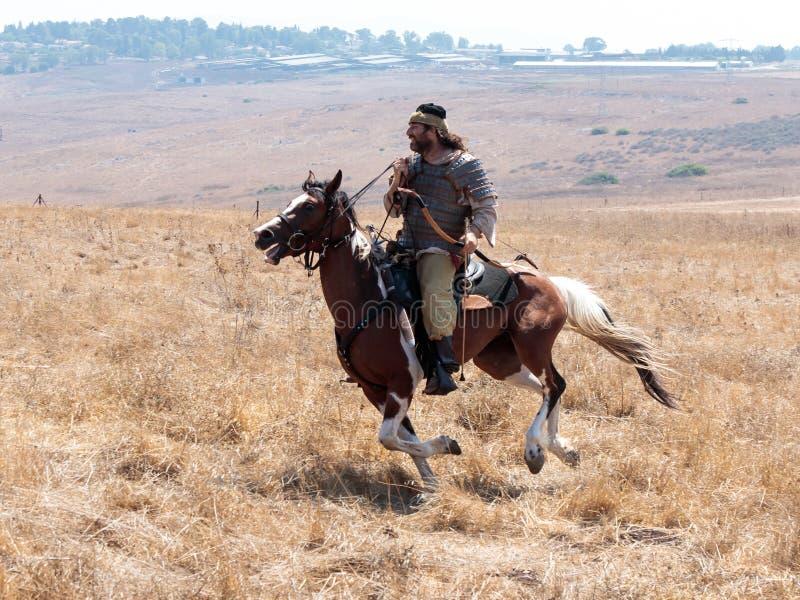 I partecipanti alla ricostruzione dei corni di Hattin combattono nel 1187 muovendo intorno il campo di battaglia vicino a Tiberia immagine stock libera da diritti