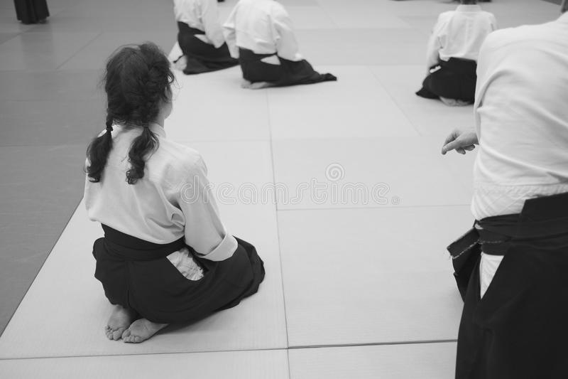I partecipanti di addestramento di aikidi si siedono su una stuoia fotografia stock