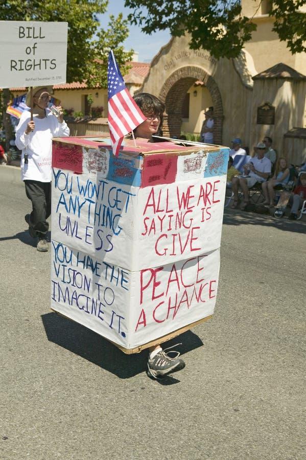 I partecipanti di parata che portano i segni circa pace fanno la loro via principale di modo giù durante il quarto della parata d fotografia stock