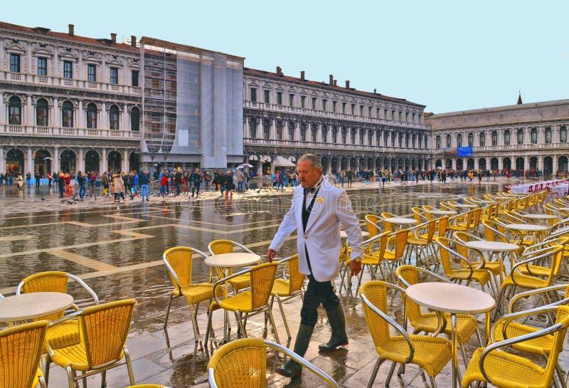 i passaggi del cameriere attraverso le sedie gialle di un café storico in mezzo al quadrato del segno di San si sono sommersi fotografia stock libera da diritti