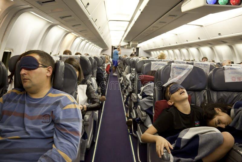 I passeggeri stanno dormendo nella cabina in volo immagine stock libera da diritti
