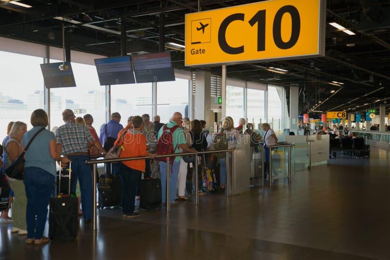 I passeggeri stanno facendo la coda per imbarcarsi su un aereo nell'area di partenza sull'aeroporto di Schiphol immagine stock libera da diritti