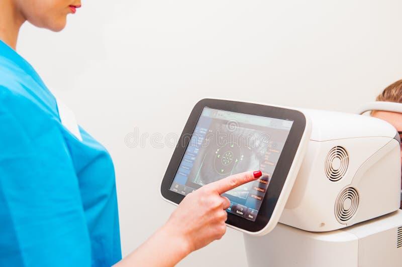 I pazienti d'esplorazione dello strumento di comandi di medico osservano nella clinica dell'oftalmologia, Automatico-riferimento- fotografie stock libere da diritti
