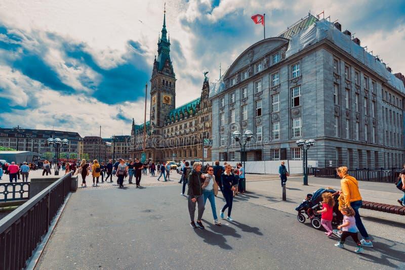 I pedestrants non identificati attraversano di mercato davanti al townhall della città immagini stock