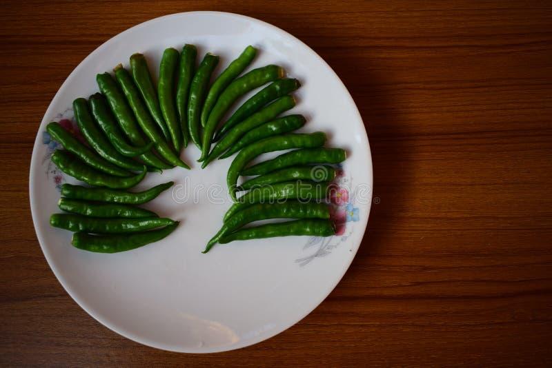 I peperoncini rossi verdi hanno sistemato nel bello modello su un piatto immagine stock libera da diritti