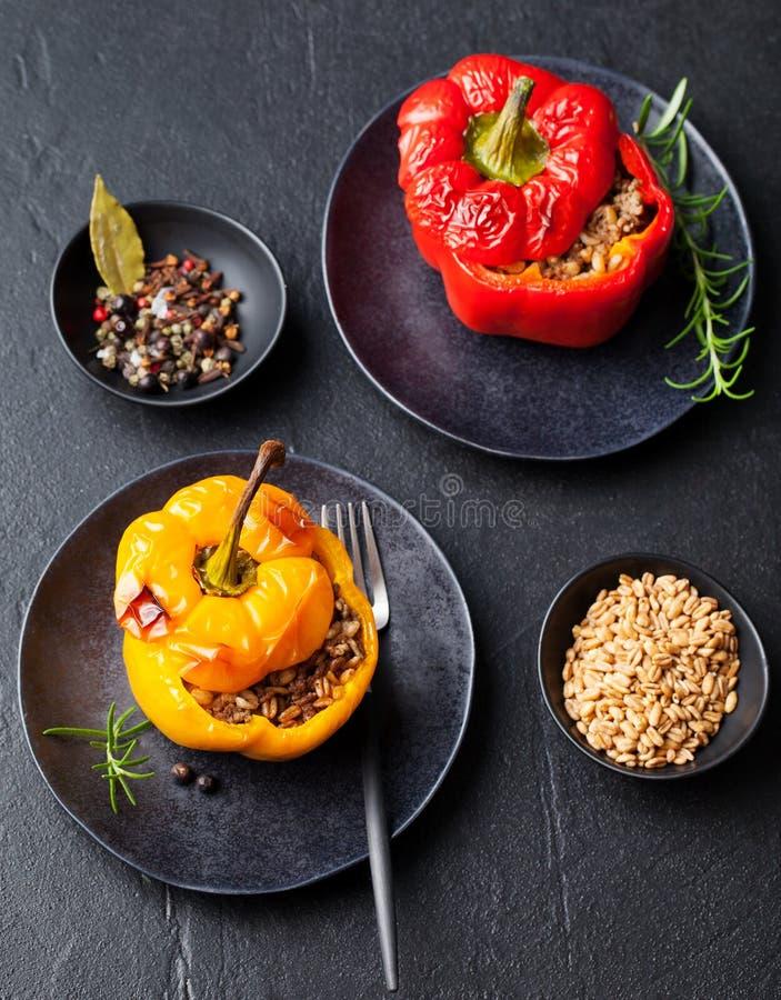 I peperoni dolci farciti al forno hanno riempito di spelta, il riso, fondo di pietra delle verdure fotografia stock libera da diritti