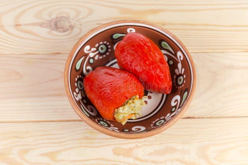 I peperoni dolci rossi farciti cucinati in un'argilla lanciano fotografia stock libera da diritti