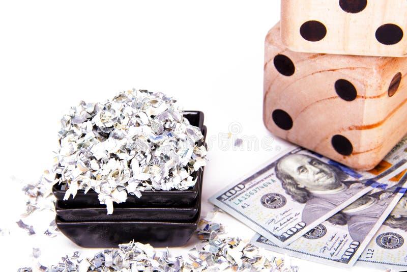 I pericoli di presa della cura dei vostri soldi Fondo di soldi tagliuzzati accanto a cento banconote in dollari e dadi fotografia stock