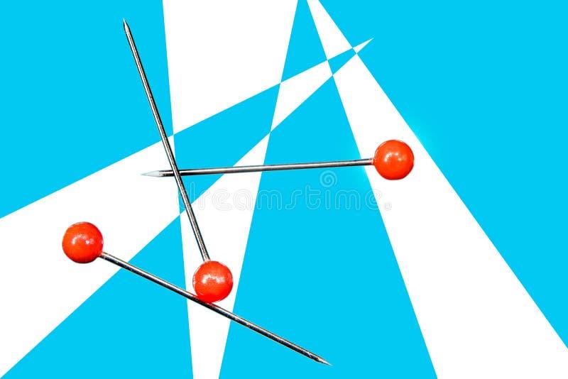 I perni con le palle rosse su fondo blu e bianco è macro immagine stock