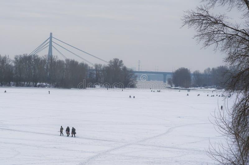 I pescatori con attrezzatura stanno pescando sul fiume Dnipro su ghiaccio nel giorno di inverno pescatori Kyiv, Ucraina immagine stock