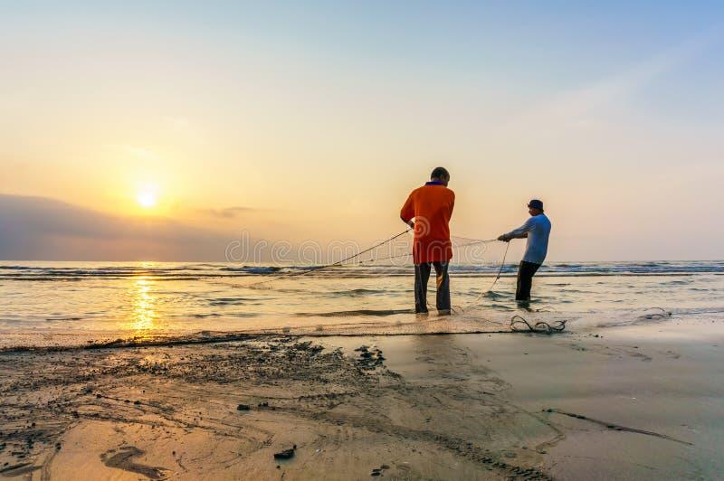 I pescatori fanno il loro lavoro vicino alla spiaggia di Beserah, Kuantan, Malesia fotografia stock