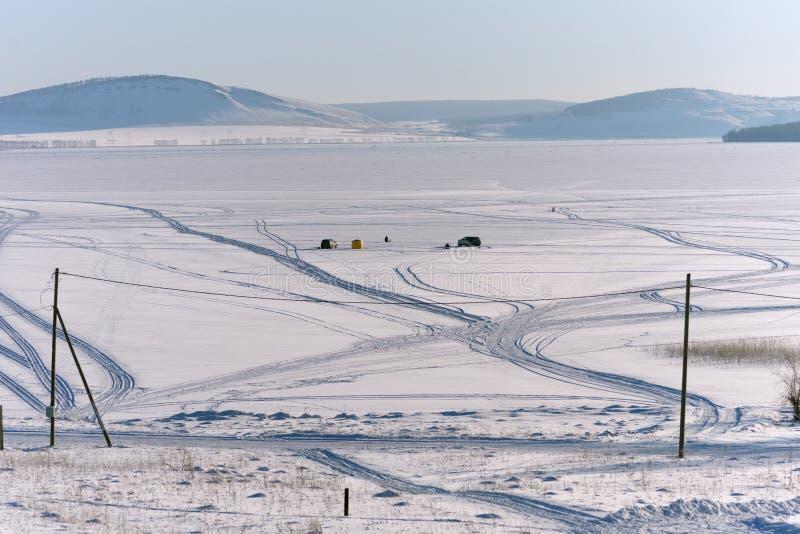 I pescatori pescano il pesce sul grande lago congelato, contro il contesto delle montagne, nell'inverno fotografia stock